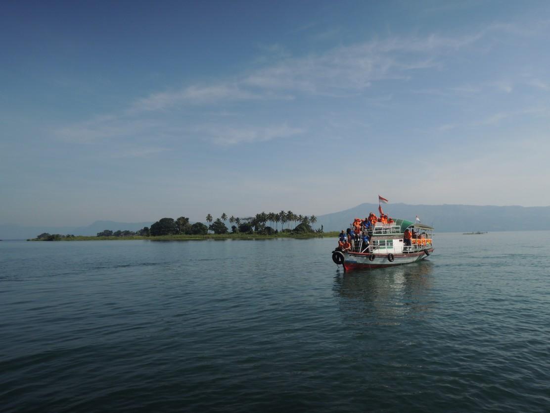 A passenger boat operates in the serene morning at Toba Lake