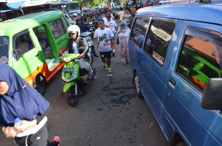 Runners race between public minivans