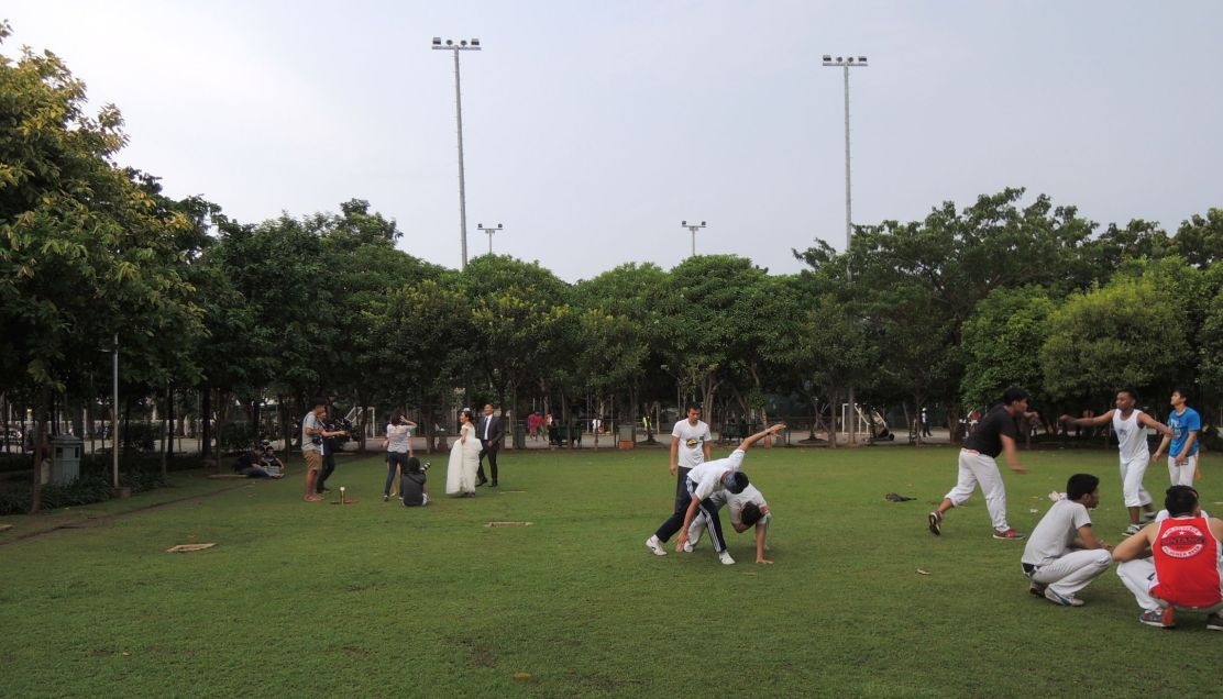 O pen field in Menteng Park is used to various p ublic activities, from Capoeira training and w edding photo session.