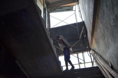 Buruh harian menapaki tangga sambil memikul sebidang keramik.
